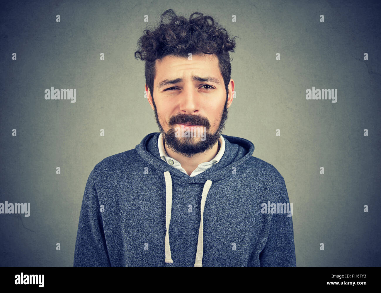 Handsome young beard man looking dubious and curious on gray background - Stock Image