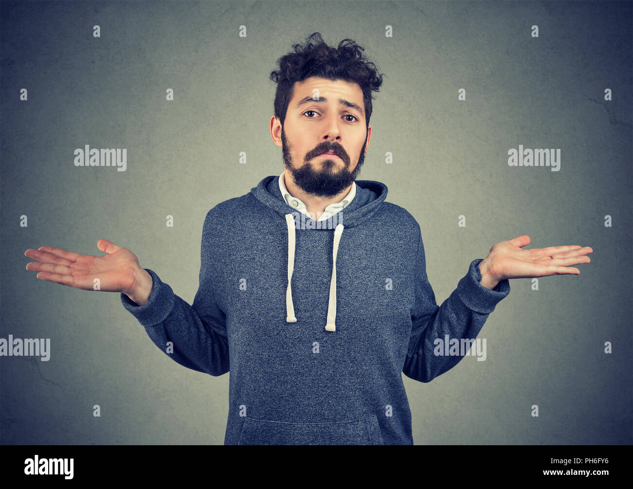 Ignorance and arrogance. Portrait of a young man shrugging shoulders feeling clueless isolated on gray background. Whatever attitude reaction - Stock Image