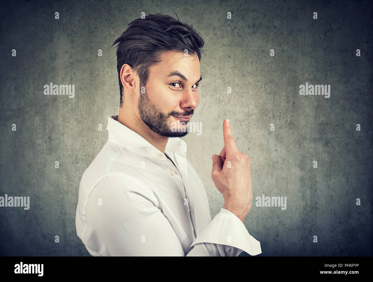 Handsome bearded man holding finger up for number one being ironic on gray background - Stock Image