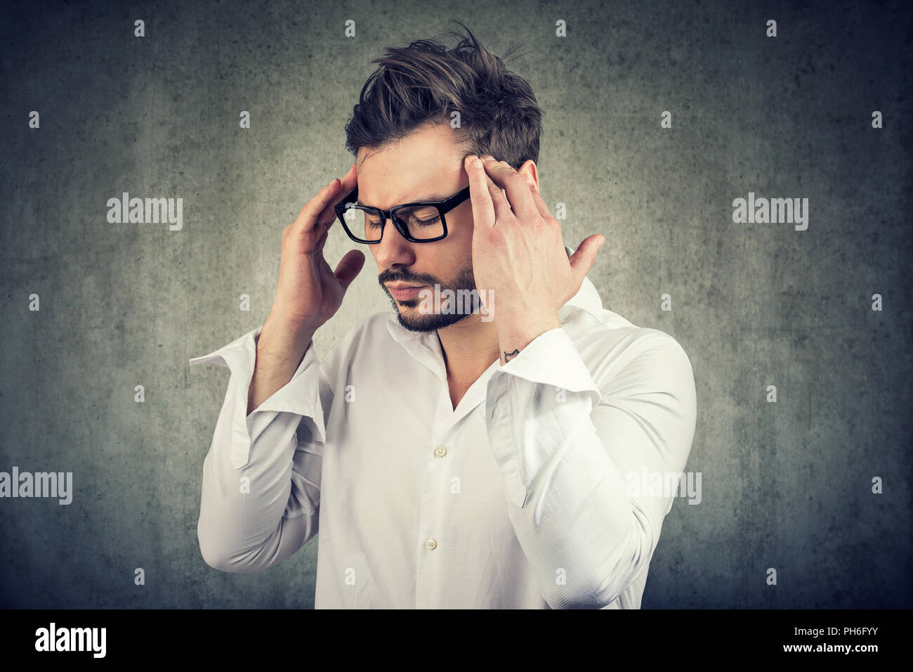 Adult man in glasses holding fingers on temples trying to concentrate on decision making - Stock Image