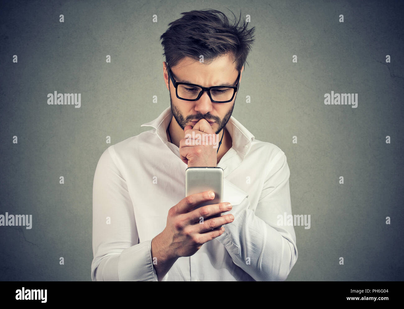 Clueless young man having troubles with his smartphone looking preoccupied - Stock Image