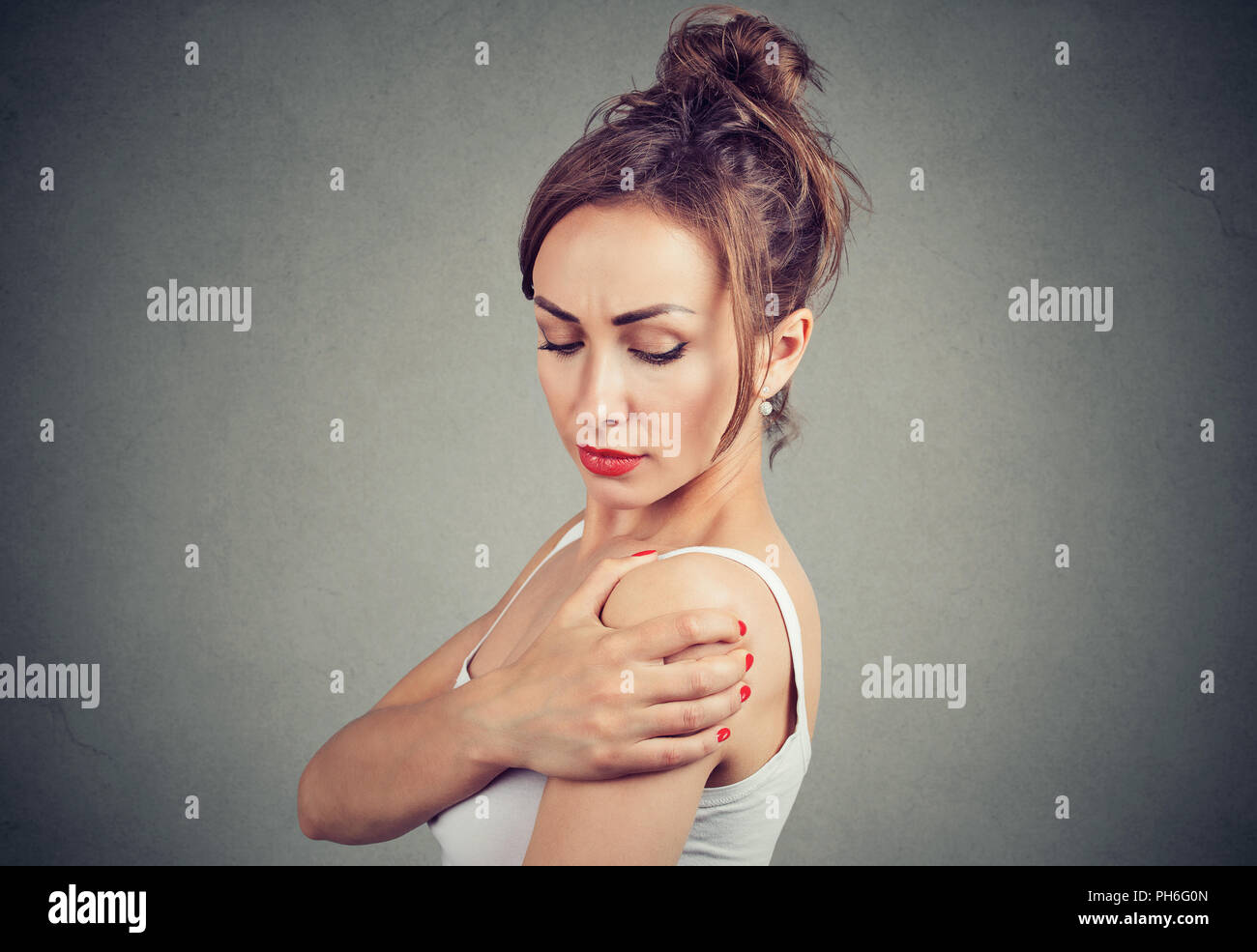 Young brunette rubbing shoulder having pain in joint and standing on gray background - Stock Image