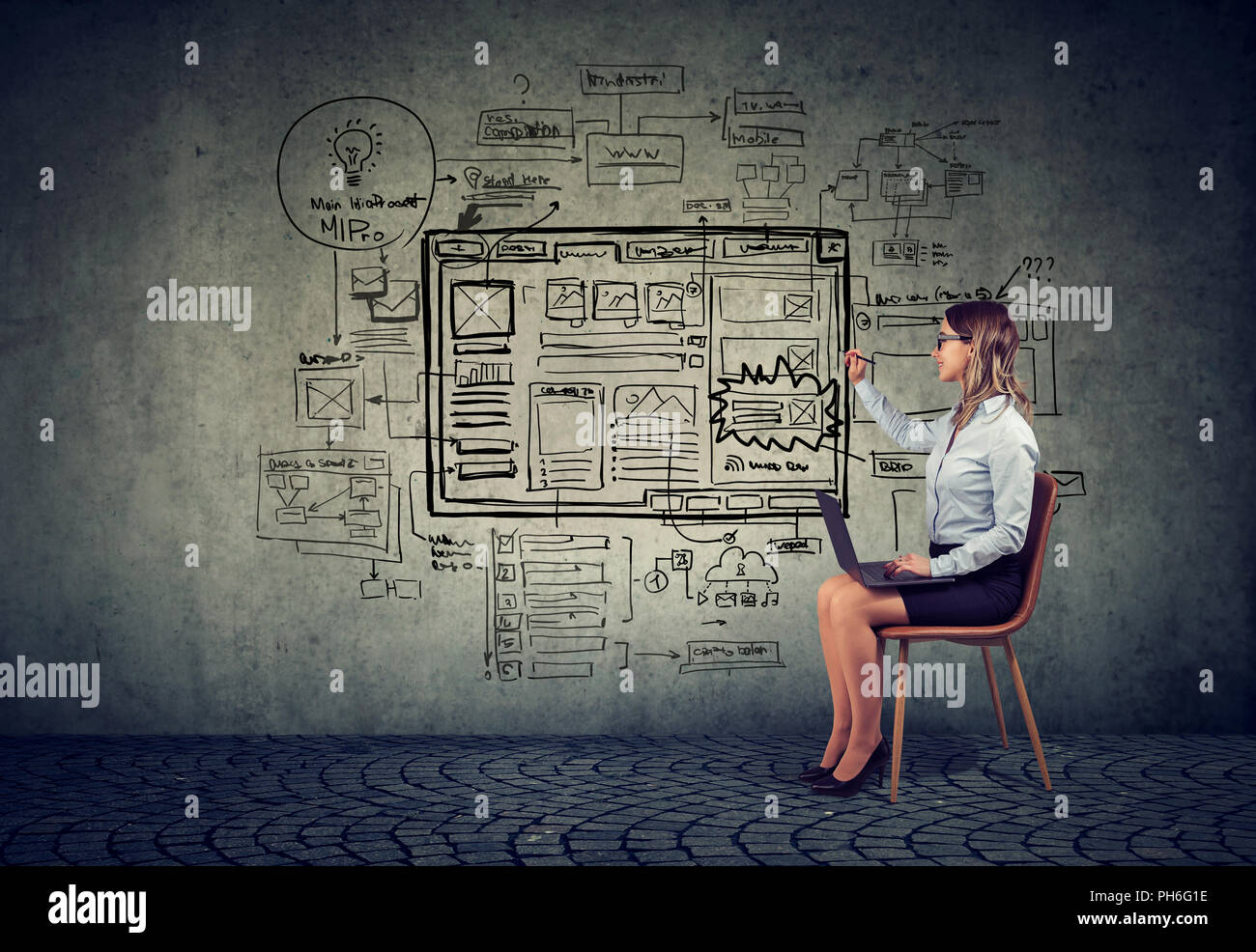 Business woman using laptop drawing new startup internet web site project on a wall - Stock Image