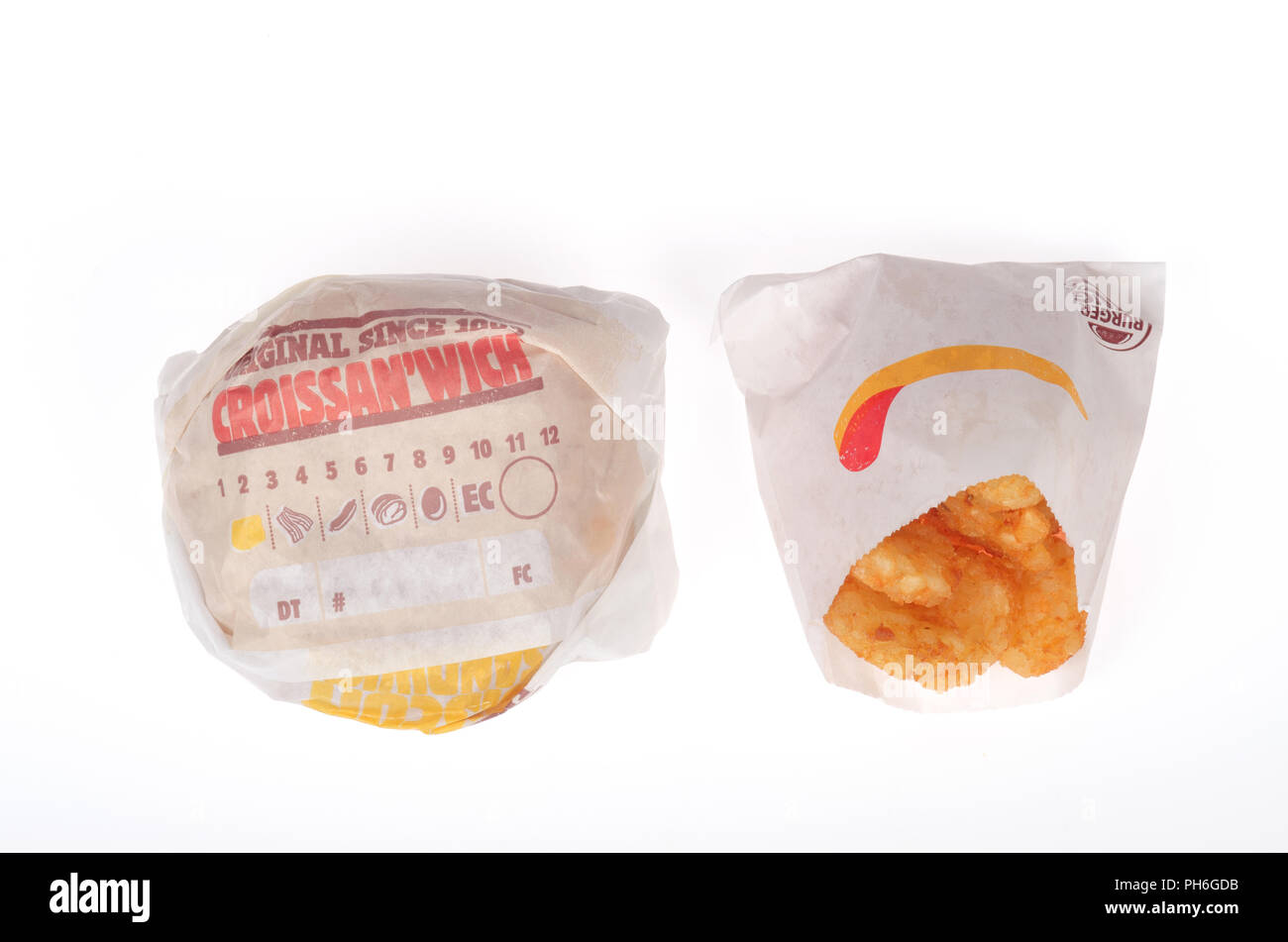 Burger King sausage, egg and cheese Croissan'wich and hash browns in wrappers on white background - Stock Image