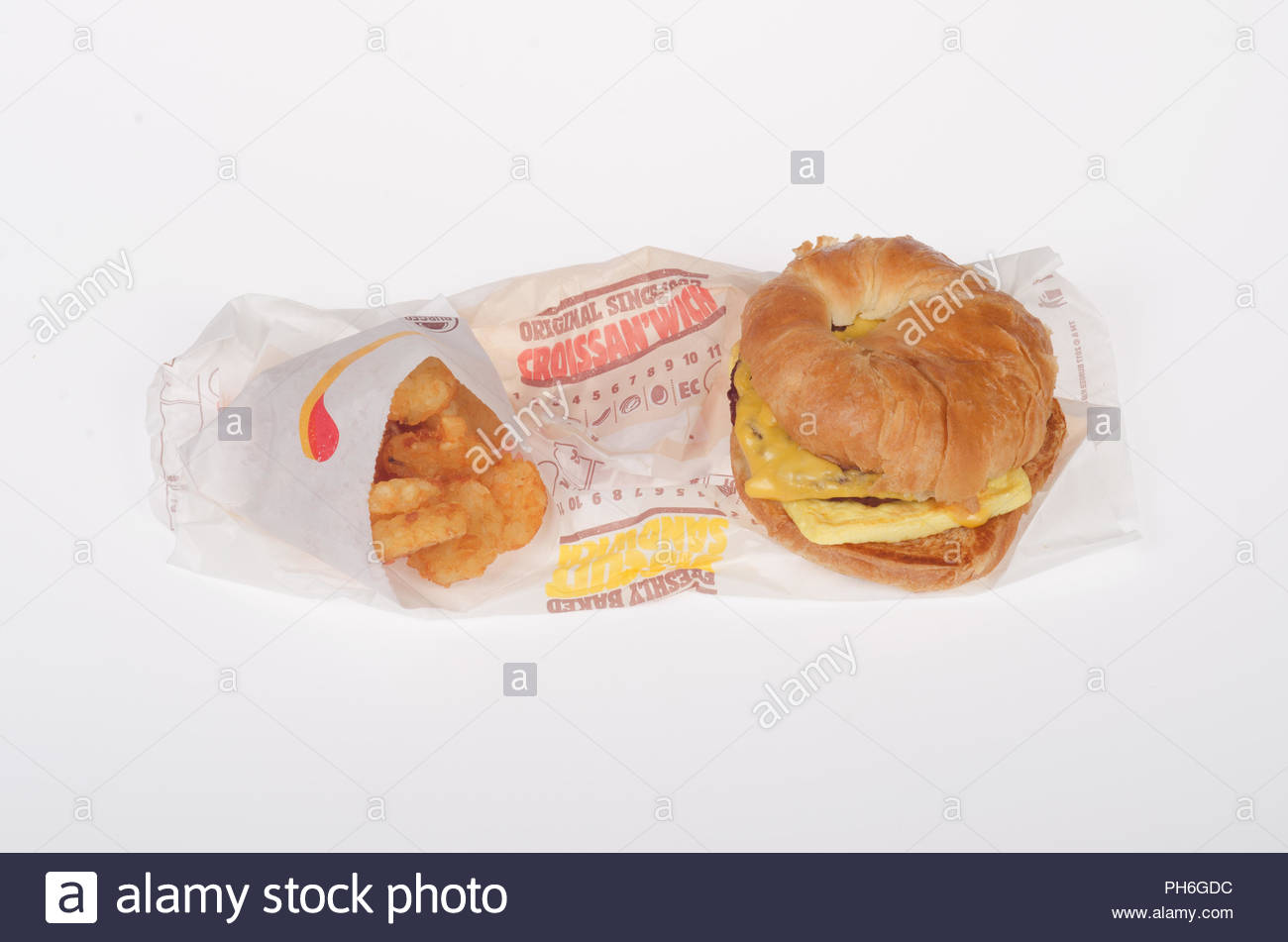 Burger King Sausage and Cheese Croissan'wich and hash browns breakfast meal with wrappers on white background - Stock Image