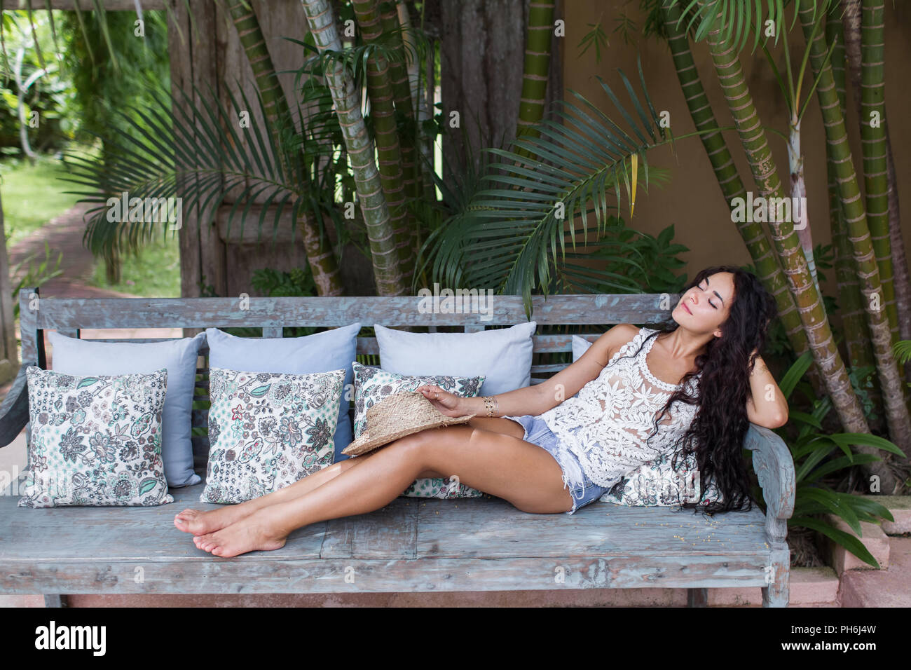 Beautiful young woman with long black hair relaxing on sofa with straw hat - Stock Image