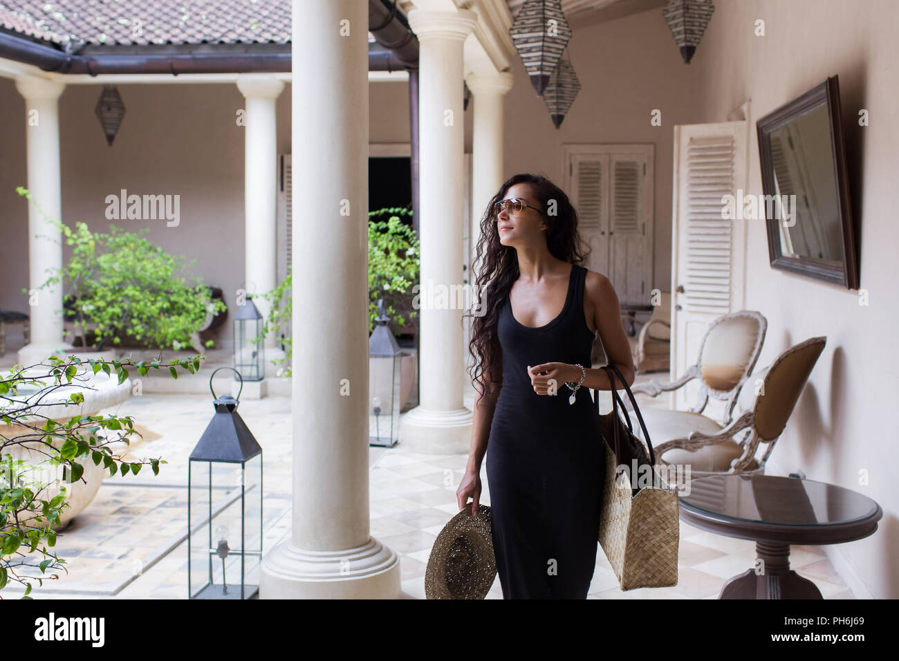 Pleased woman in black dress after shopping with straw bag in luxury mall with white walls and columns - Stock Image