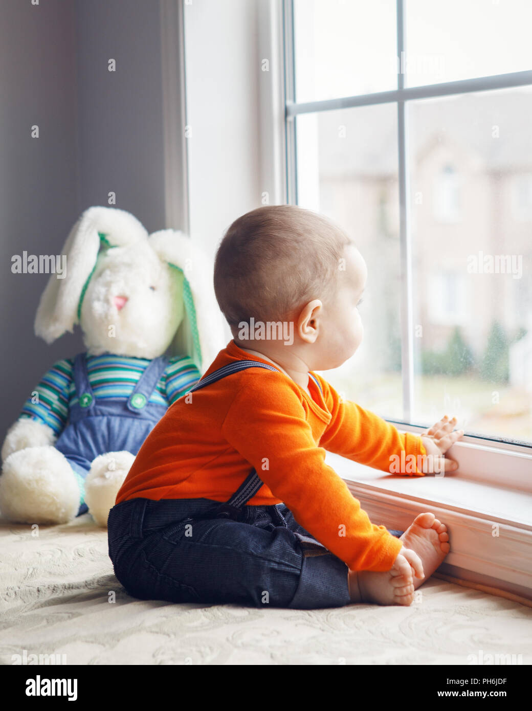 a9c6c4015 Portrait of cute adorable Caucasian baby boy in orange shirt onesie, jeans  with suspenders barefoot sitting with bunny toy on windowsill looking away,