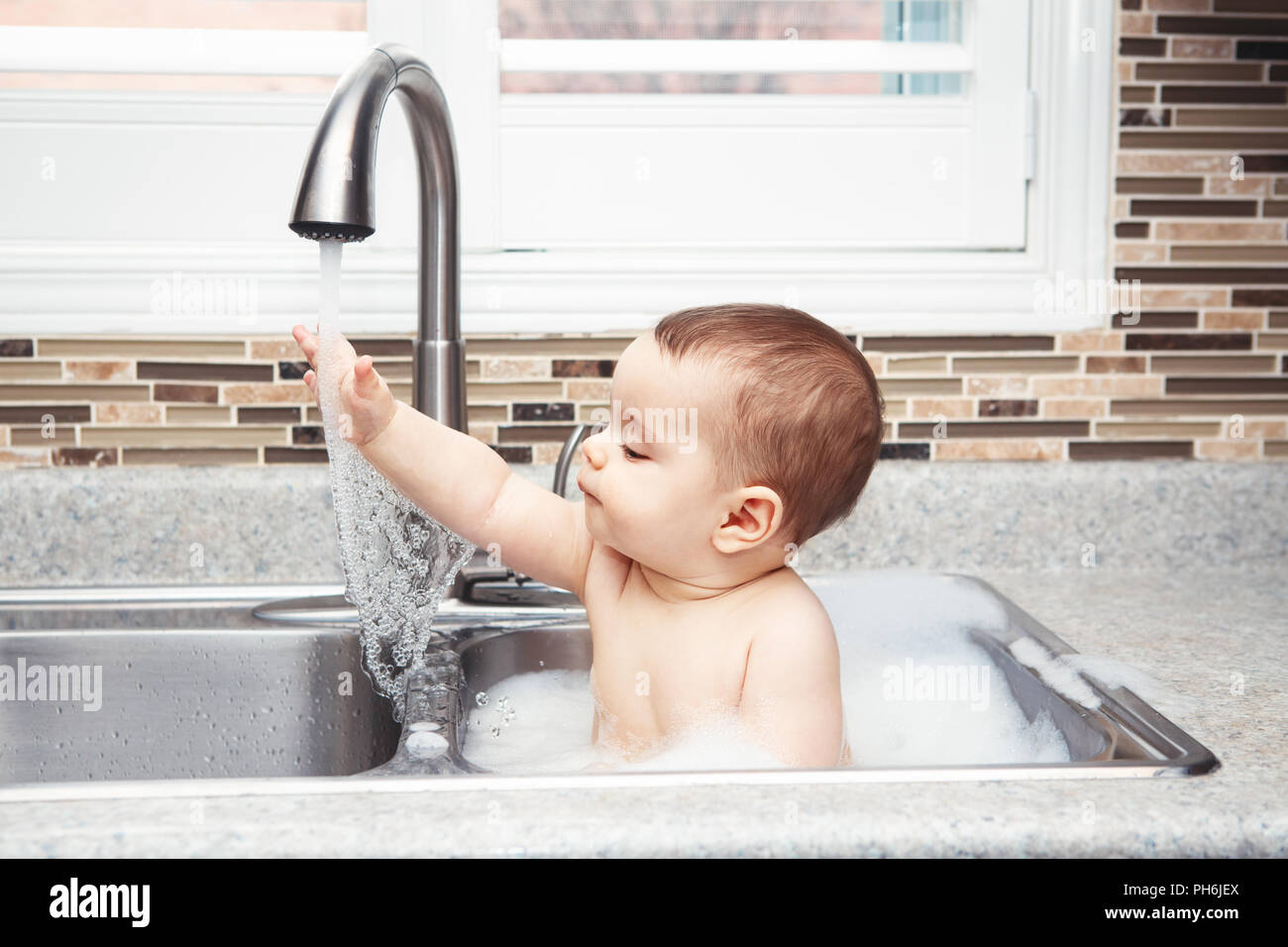 Portrait of cute Caucasian funny baby girl boy with dark black eyes sitting in big kitchen sink with water and foam near window looking away, lifestyl - Stock Image