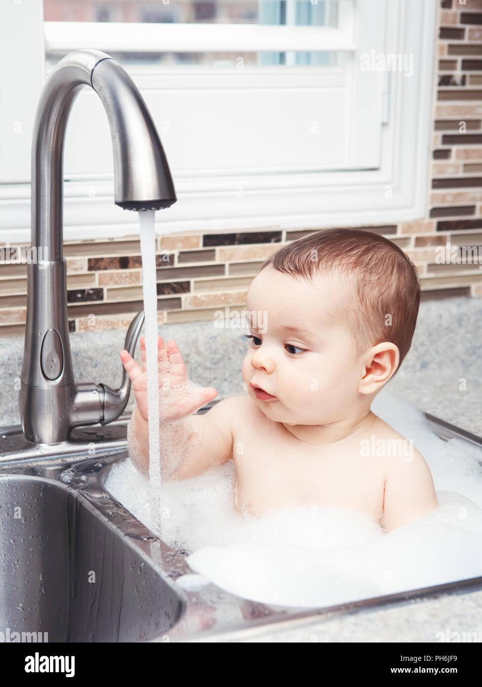 Portrait Of Cute Caucasian Funny Baby Girl Boy With Dark Black Eyes Sitting  In Big Kitchen