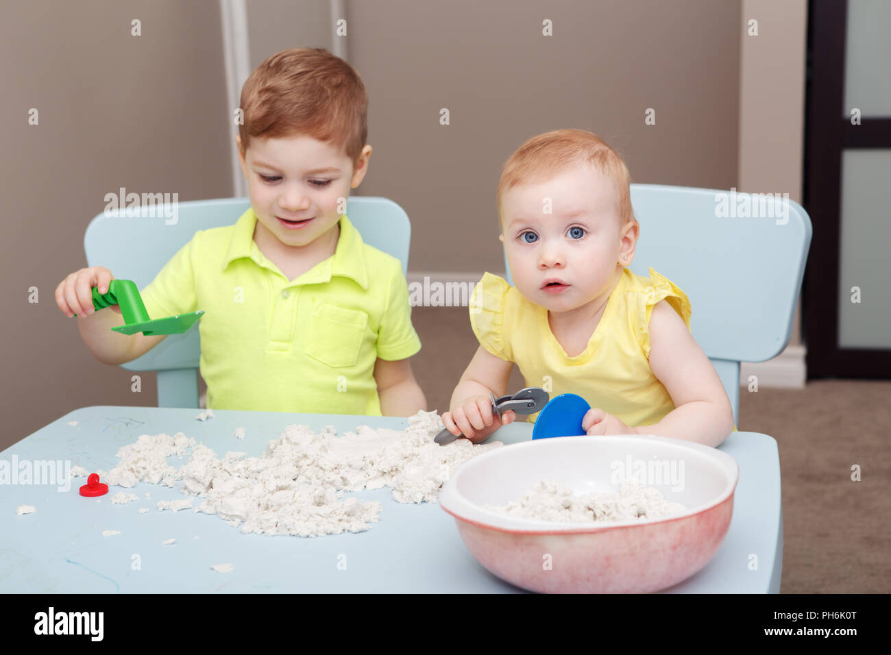 Group portrait of two cute siblings children playing kinetic sand or playdough together in kindergarden. Early creativity brain development concept. L - Stock Image