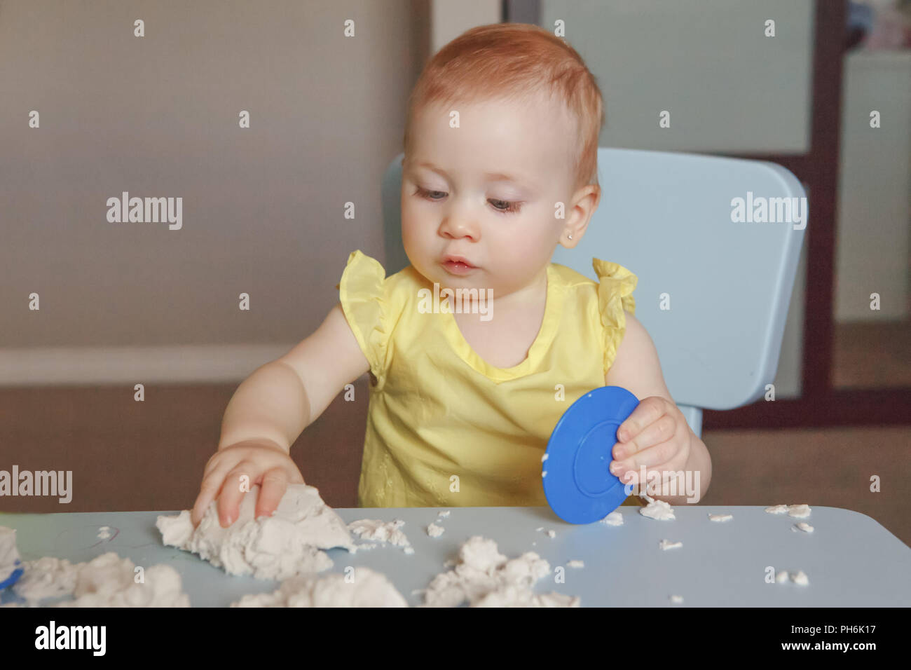 Portrait of funny cute white Caucasian baby playing kinetic sand indoors  at kindergarden. Early creativity brain development concept. Children home a - Stock Image