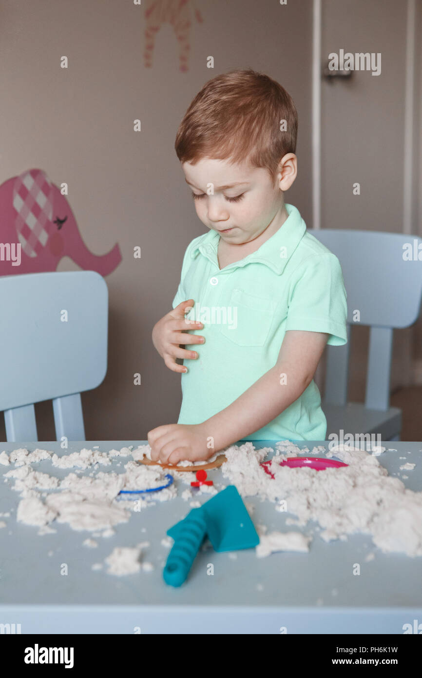 Portrait of funny cute white Caucasian boy playing kinetic sand indoors  at kindergarden. Early creativity brain development concept. Children home ac - Stock Image