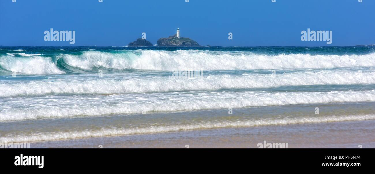 Waves rolling in on Riviere Towans beach with Godrevy lighthouse in the distance, Phillack, Hayle,cornwall,England,UK - Stock Image
