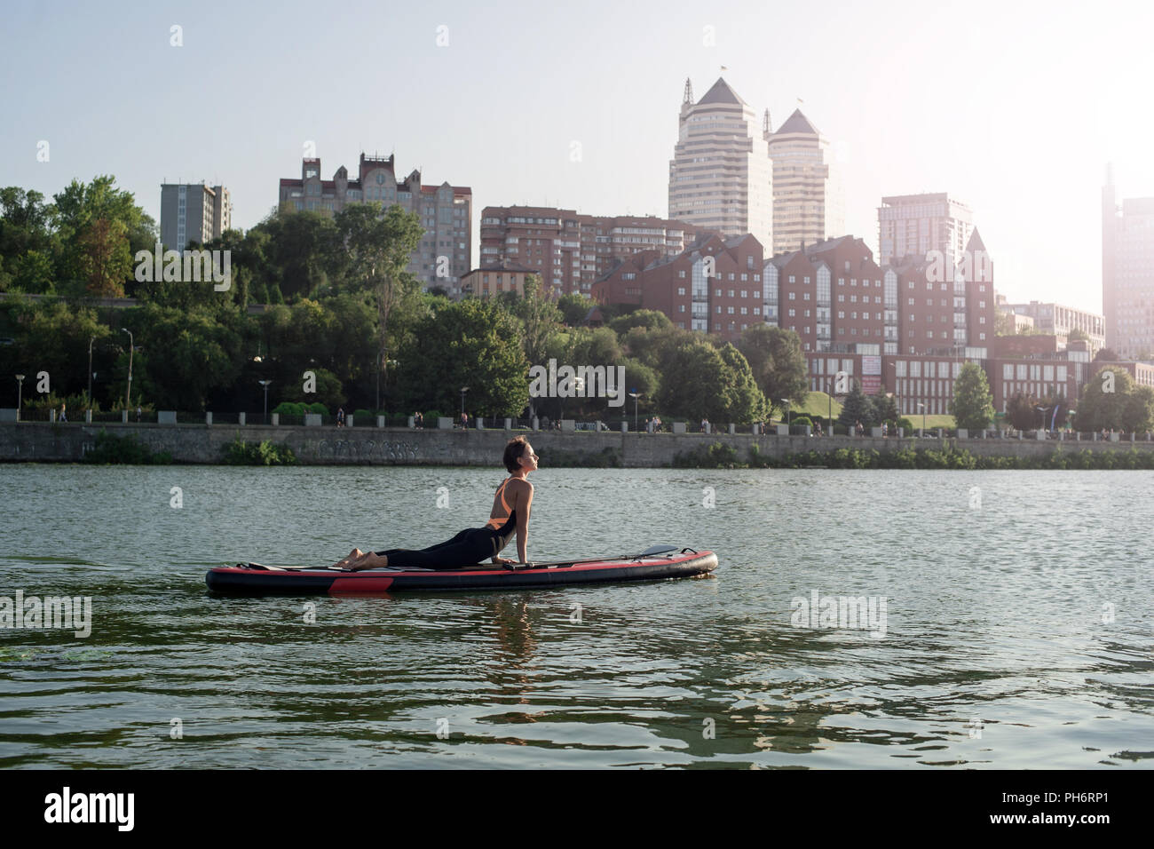 yoga on sup board, silhouette of woman on the beach - Stock Image