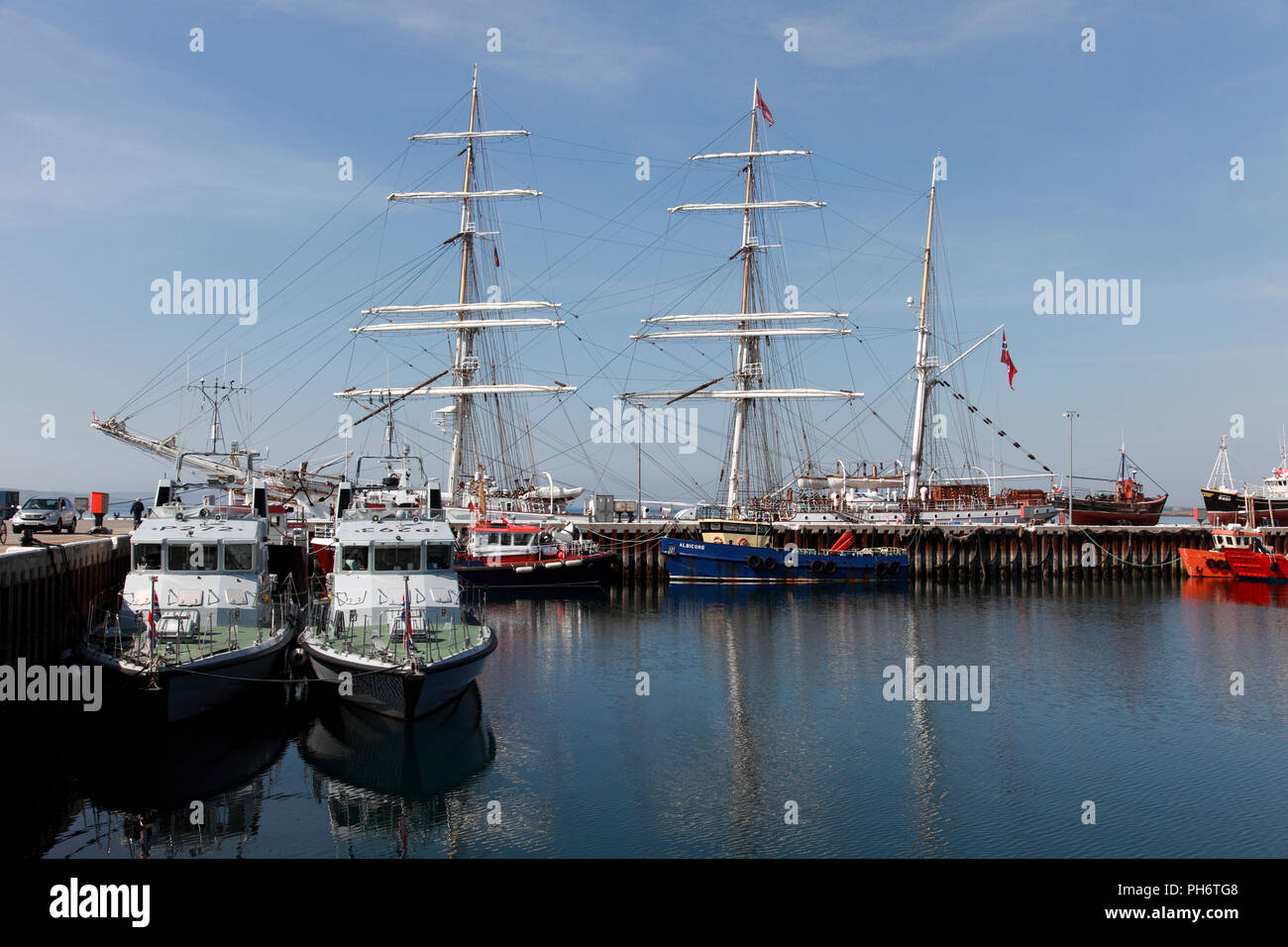Boats in Kirkwall harbour, including fast training boats, fishing boats and a three-masted tall ship, Orkney, Scotland - Stock Image