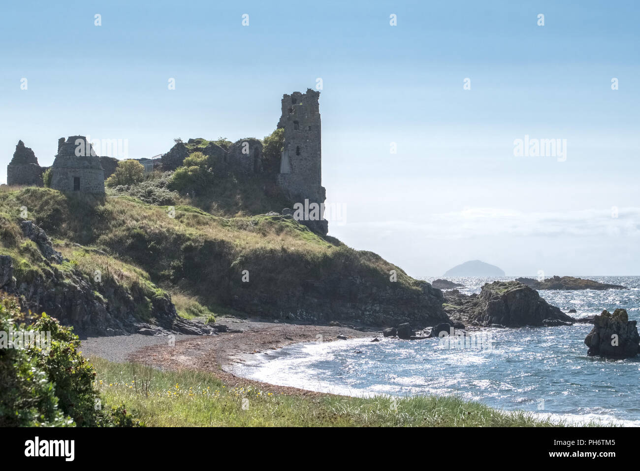 The ancient ruins of Castle Dunure with Ailsa Craig in the hazy distance taken on a warm  hazy sunny day and is a good image for Scotland's tourism. - Stock Image