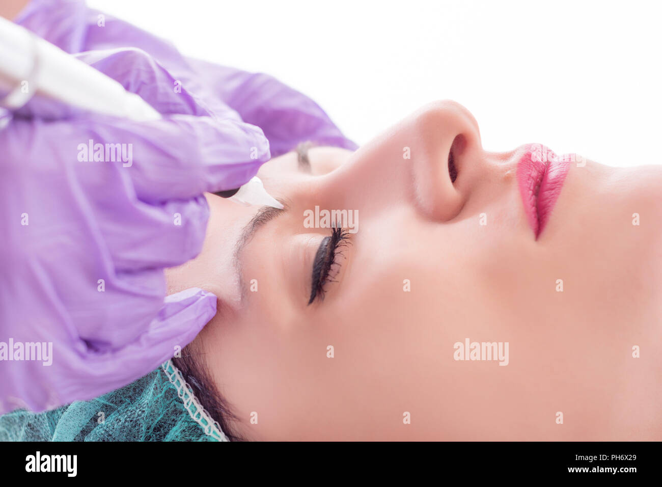 Applying permanent make up on eyebrows in beauty studio on young woman. Cosmetologist tattooing with professional tool. Close up, selective focus - Stock Image