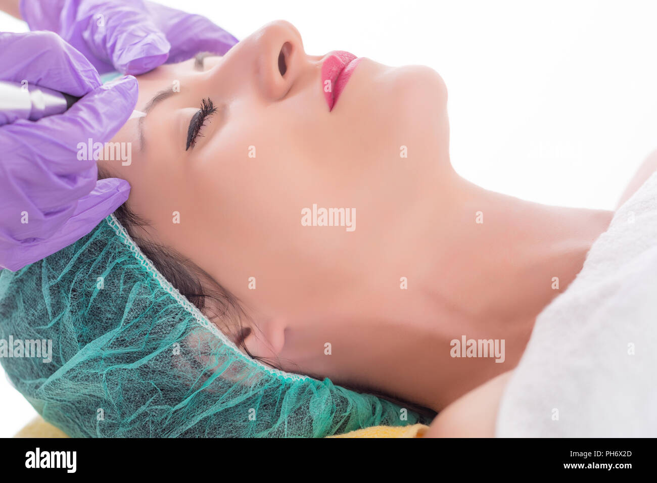 Micro pigmentation or permanent make up on eyebrow. Beautician applying tattoo with professional tool in beauty studio. Close up, selective focus - Stock Image