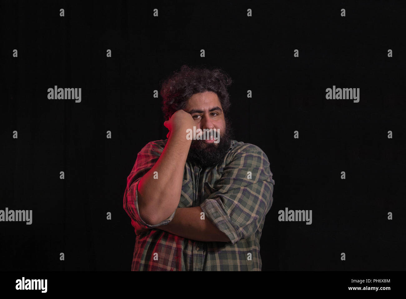 Big man with thick beard in a skeptical pose - Stock Image