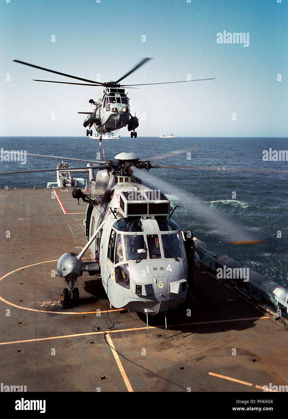 AJAXNETPHOTO. 6TH OCT 2001. OMAN. A SEA KING HELICOPTER FROM ROYAL NAVAL AIR SQUADRON 845 LIFTS OFF FROM THE DECK OF HMS FEARLESS AS A LYNX PREPARES TO FOLLOW. PHOTO:JONATHAN EASTLAND/AJAXREF:CD/SS/SH1-6(OMA-18) Stock Photo