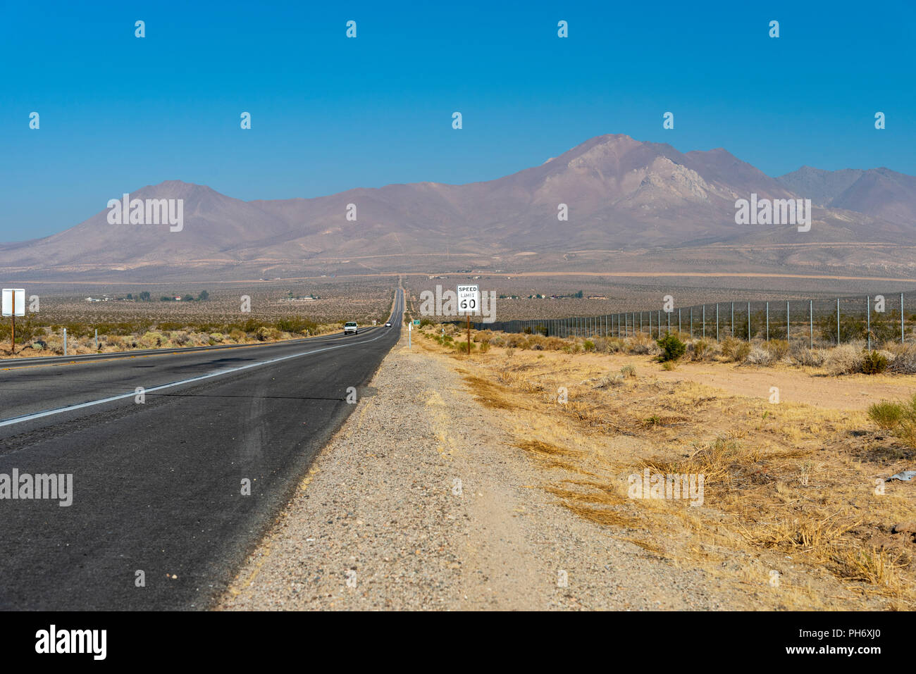 Desert highway with speed limit sign leading towards tall barren mountains under a bight blue sky. Gravel roadside and dead vegetation. Stock Photo