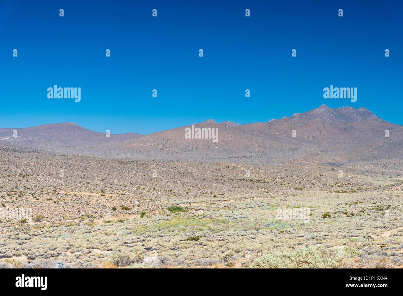 'Vast desert valley with barren mountains under blue sky. - Stock Image