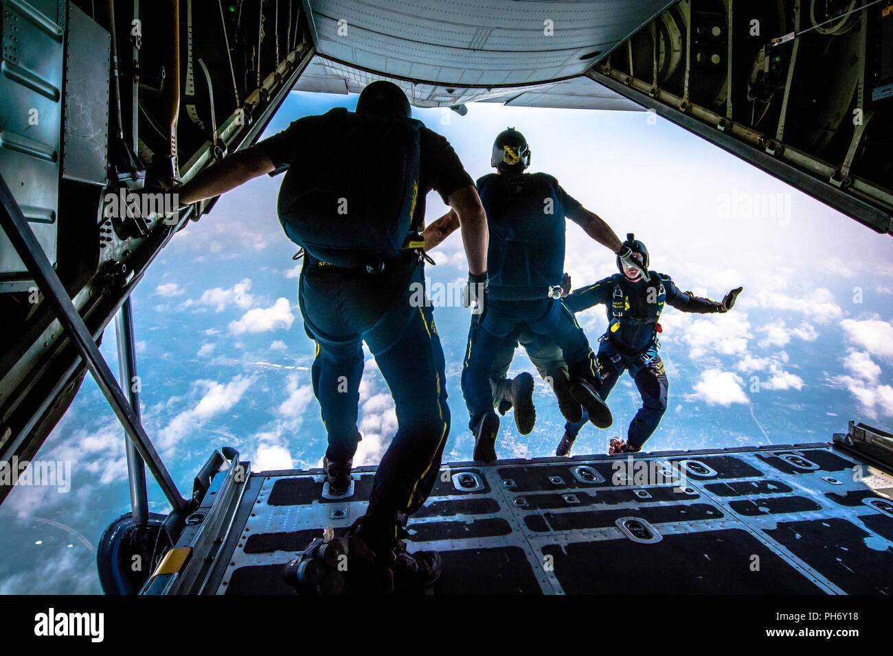 The U.S. Navy Leap Frogs jump from a C-130 Hercules aircraft during the Sound of Speed Air Show and Open House above Rosecrans Air National Guard Base, St. Joseph, Mo., August 24, 2018. The air show was hosted by the 139th Airlift Wing and city of St. Joseph to thank the community for their support. The air show committee estimated around 70,000 people attended during the weekend performances. (U.S. Air National Guard photo by Staff Sgt. Patrick Evenson) - Stock Image