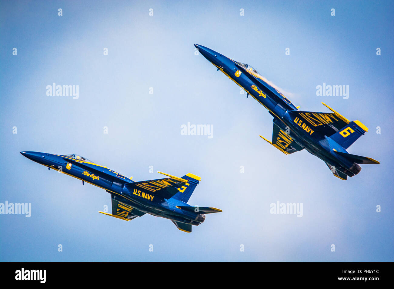 A formation of U.S. Navy F-18 Hornets, assigned to the Navy Flight Demonstration Squadron, the Blue Angels, fly over a C-130 Hercules aircraft during the Sound of Speed Air Show and Open House at Rosecrans Air National Guard Base, St. Joseph, August 24, 2018. The air show was hosted by the 139th Airlift Wing, Missouri Air National Guard and city of St. Joseph to thank the community for their support. The air show committee estimated around 70,000 people attended the weekend performances. The Blue Angels strive to showcase the pride and professionalism of the United States Navy and Marine Corps - Stock Image