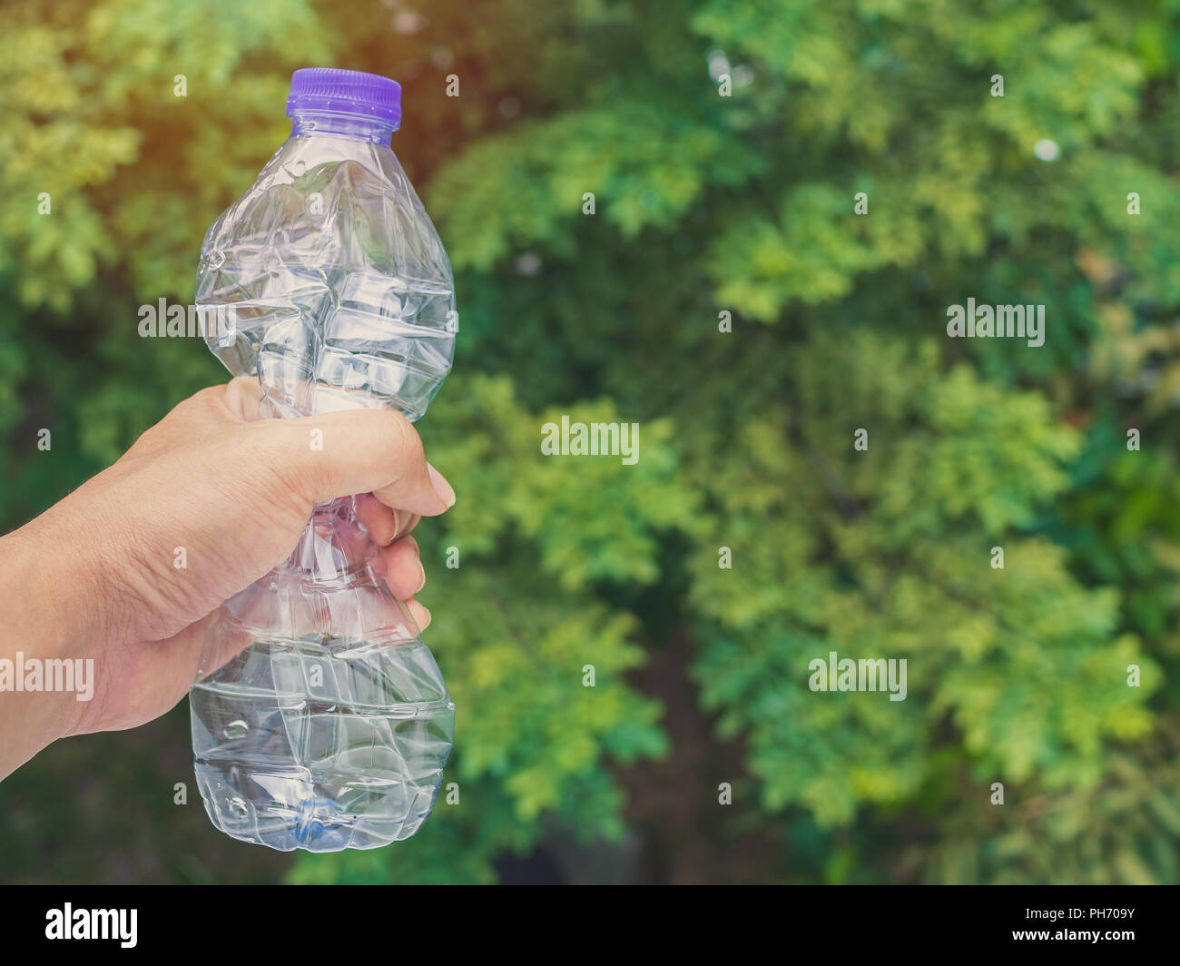 Hand squeezing recycle clear plastic drink water bottle on green nature background with copy space. - Stock Image