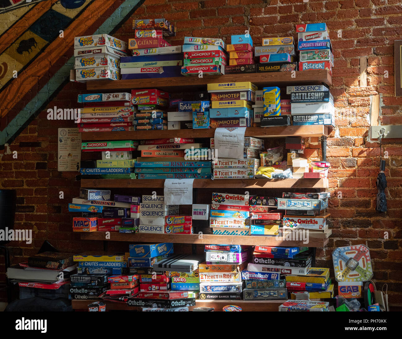 Wall of board games in a local bar - Stock Image