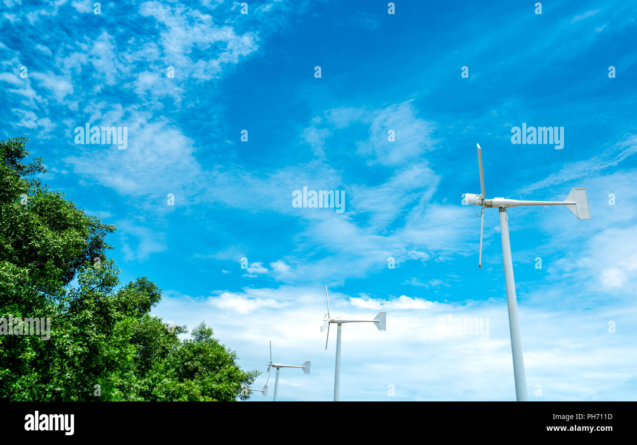 Horizontal axis wind turbine with blue sky and white clouds near green tree. Wind energy in eco wind farm. Green energy concept. Renewal energy. Alter - Stock Image