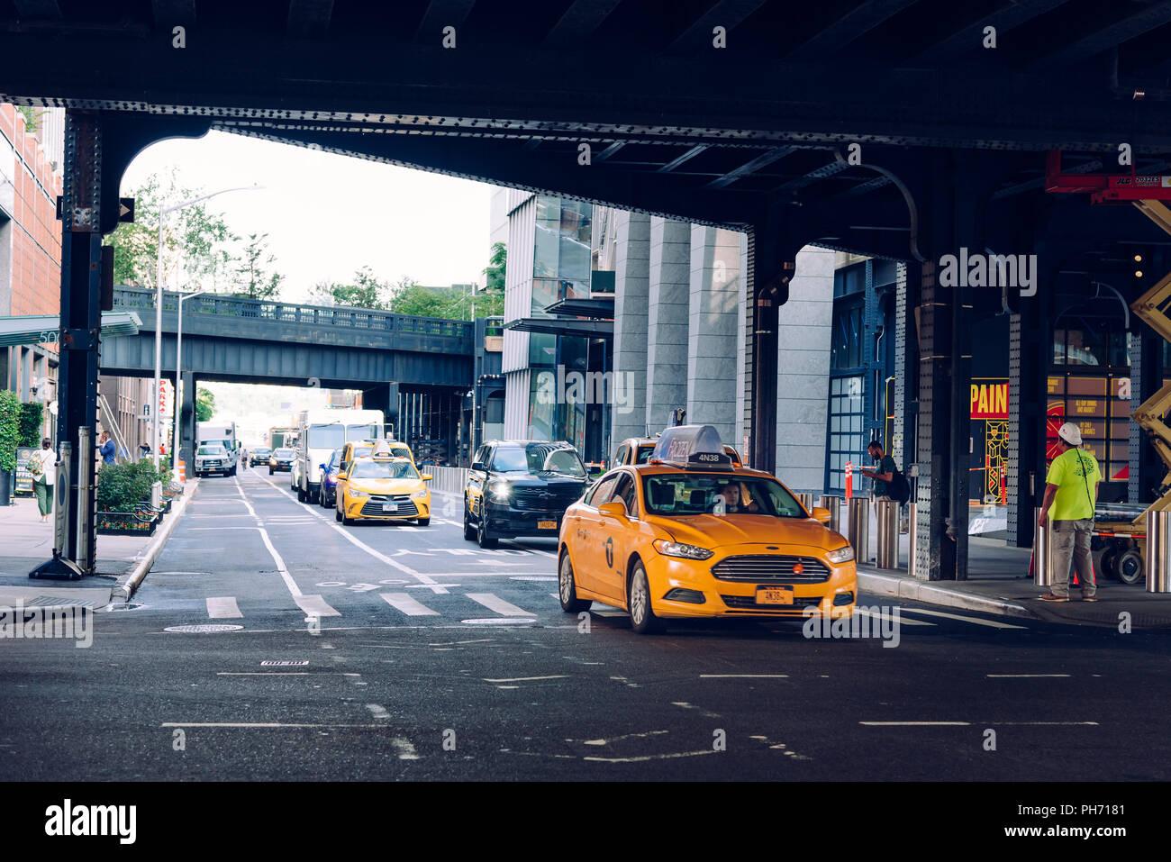 New York City, USA - June 22, 2018: Yellow taxi cab traveling under High Line bridge in Manhattan Stock Photo