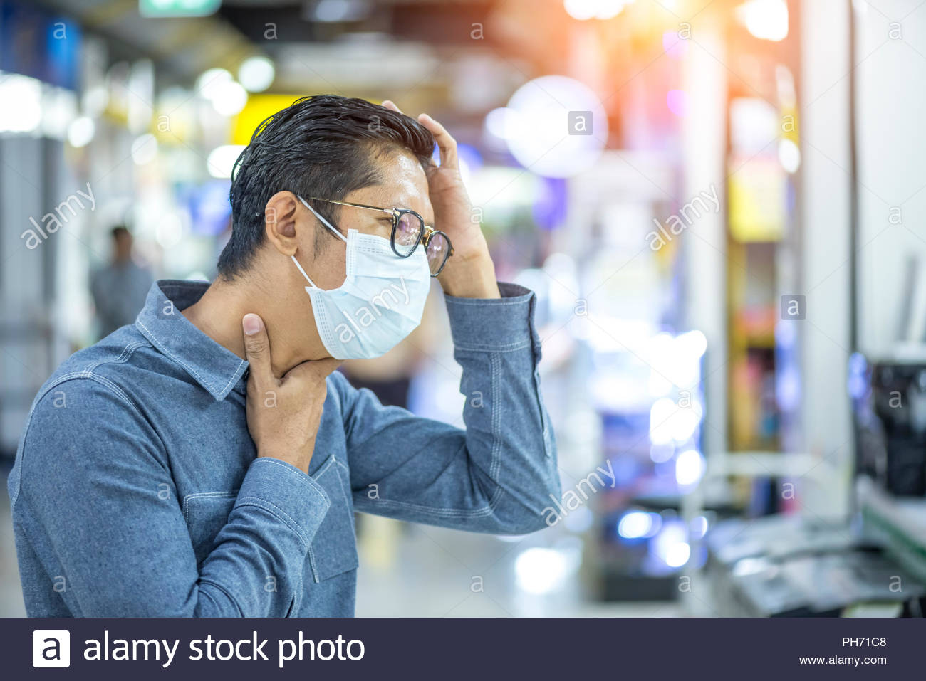 Young man sick and coughing in the public areas, Sick of the flu concept - Stock Image