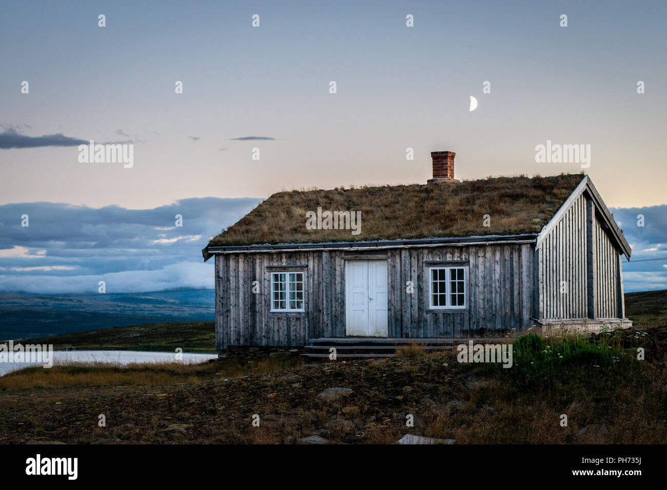 An old house with the moon just above the chimney at sunset in Storwartz, just outside of Røros (Roros), Norway. - Stock Image