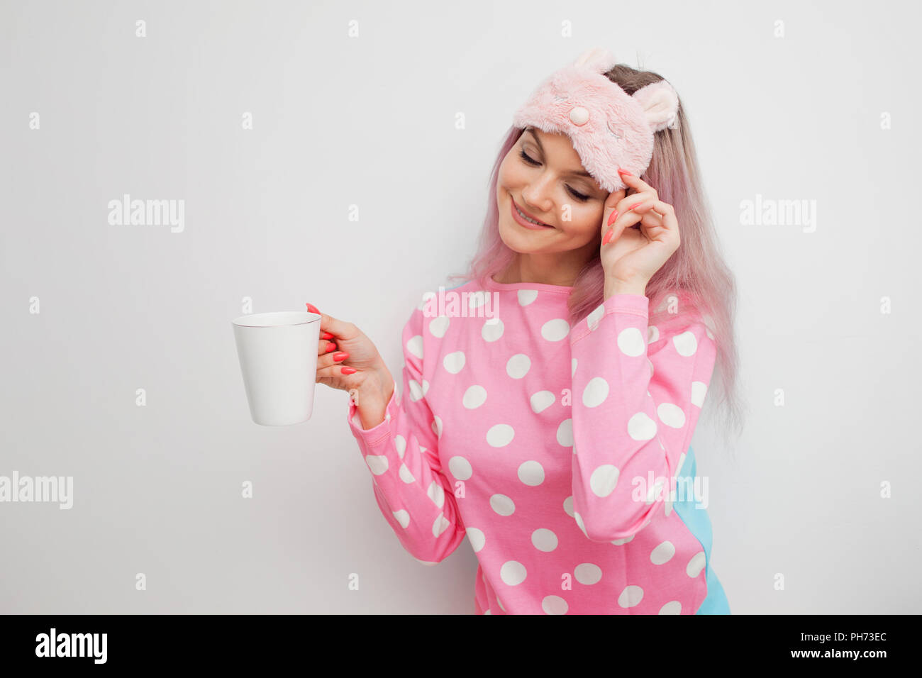 6e12fbdc7206 Smiling young woman drinking morning coffee and happy. Cute girl in pink  pajamas and sleep mask