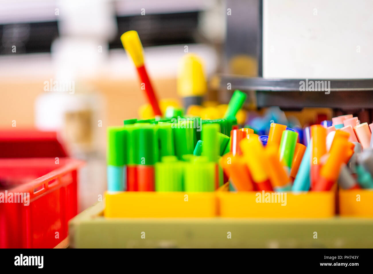 Close up image of pots of coloured pens and crayons in a school art classroom Stock Photo