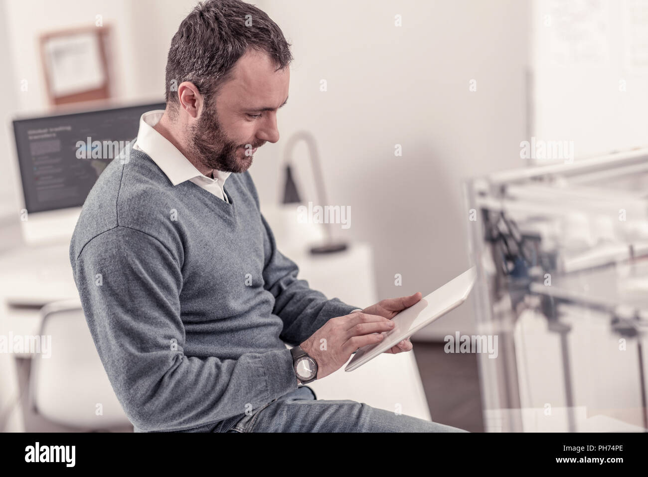 Handsome adult man sitting at the office - Stock Image