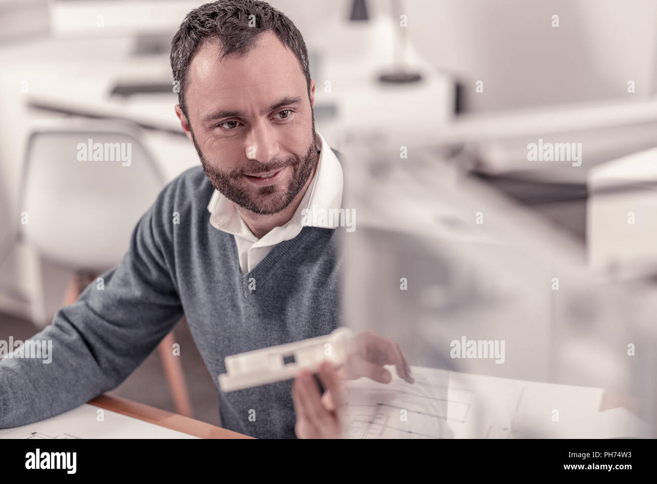 Bearded adult smiling man working at the office - Stock Image