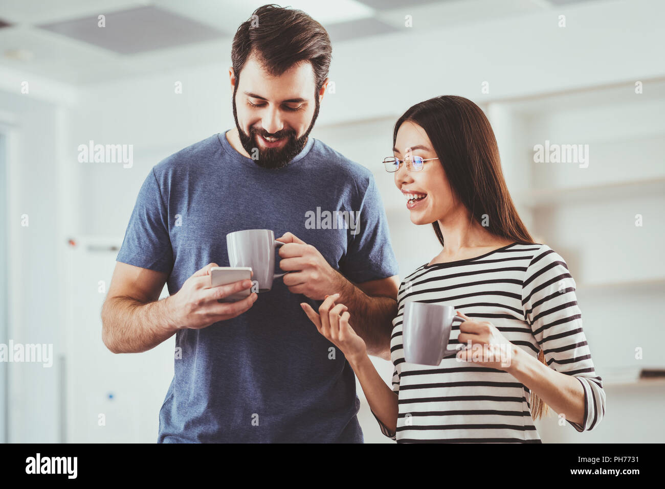 Nice pleasant man using his smartphone - Stock Image