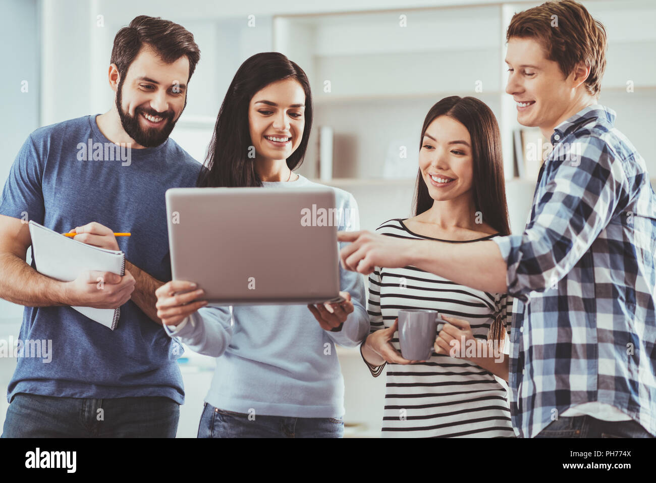 Cheerful nice woman holding a laptop - Stock Image