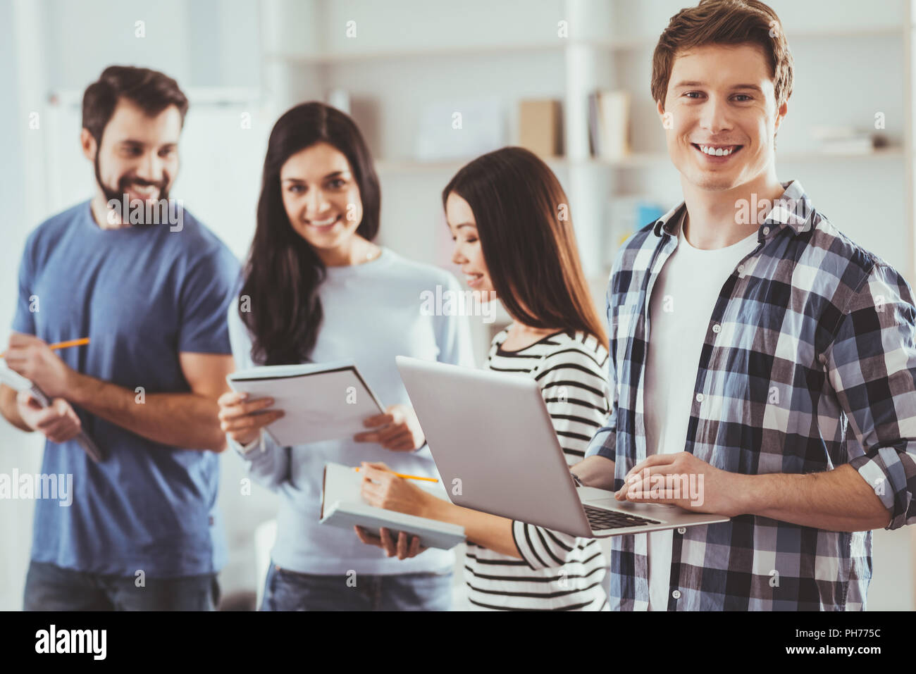 Smart young man holding a laptop - Stock Image