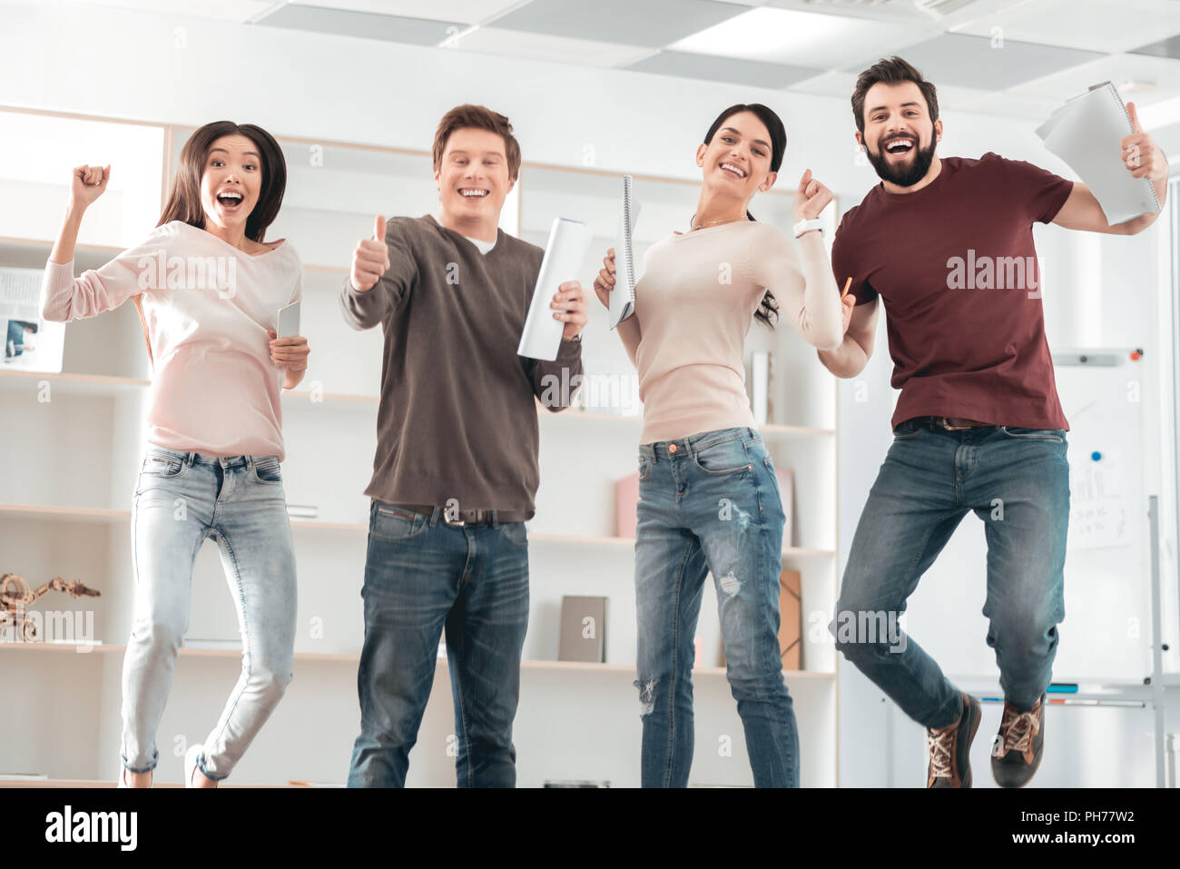 Delighted happy people jumping - Stock Image