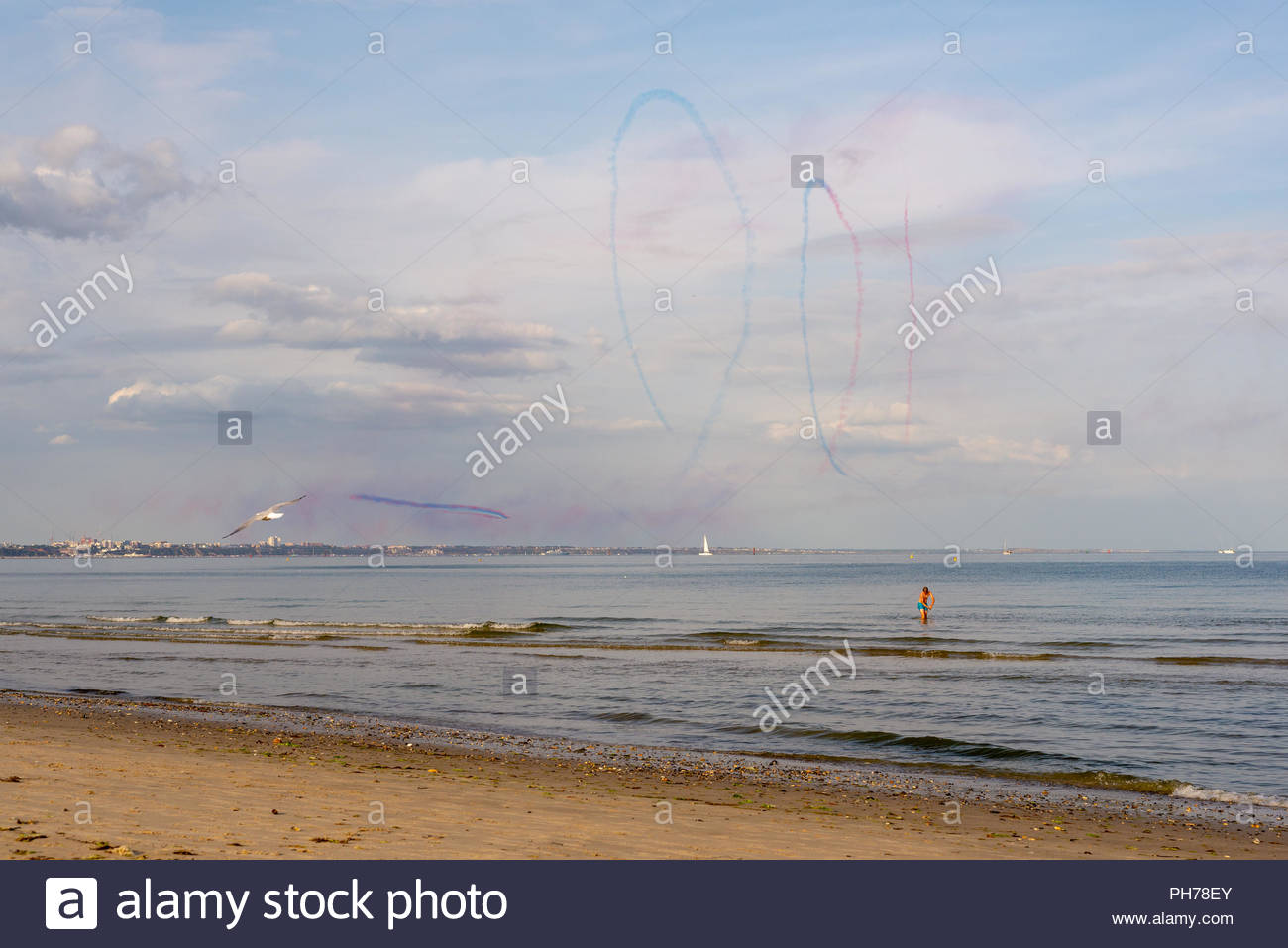 The Red Arrows aerobatic jet display team in the distance at Bournemouth Air Festival 2018 seen from Shell Bay beach, Studland, Purbeck, Dorset - Stock Image