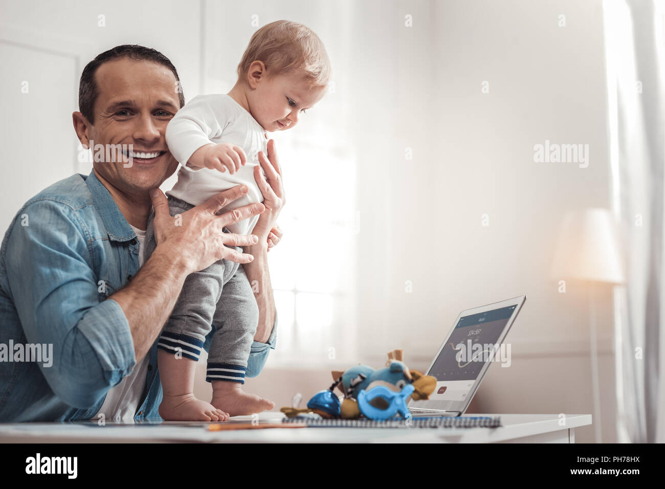 Happy cheerful man holding his child - Stock Image