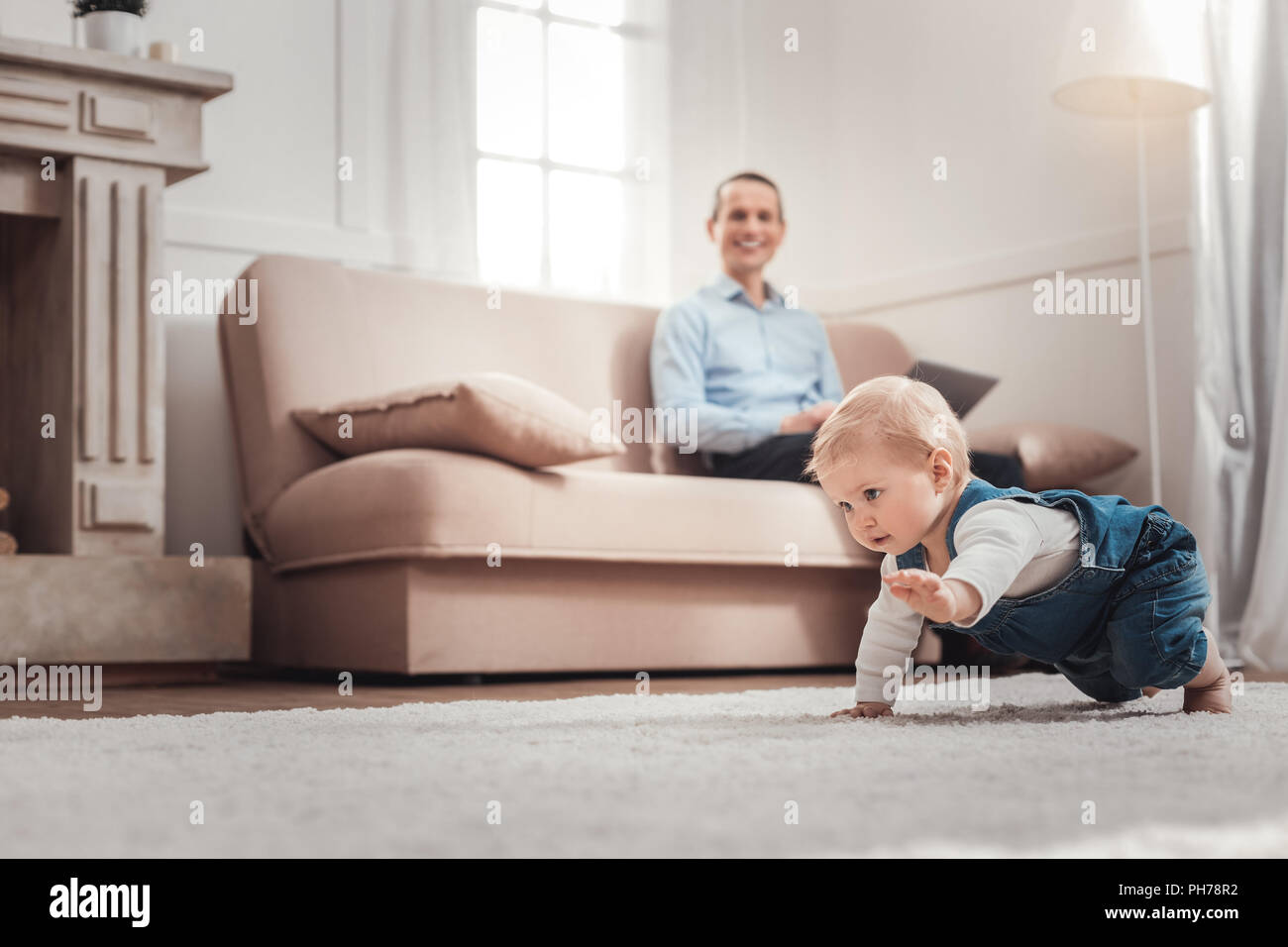 Cute positive child crawling - Stock Image
