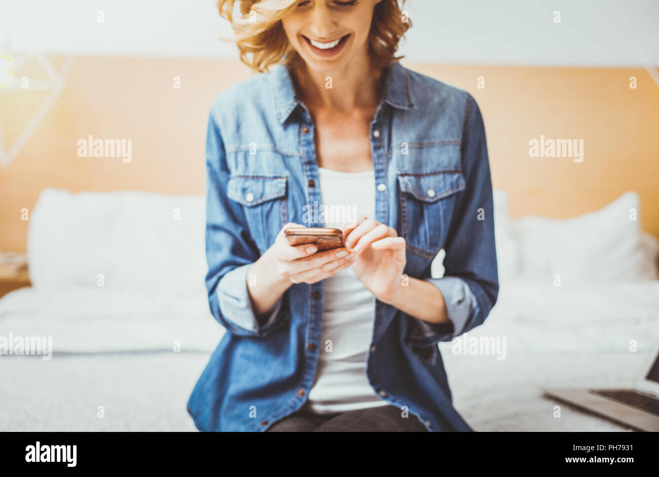 Funny woman looking at her gadget - Stock Image