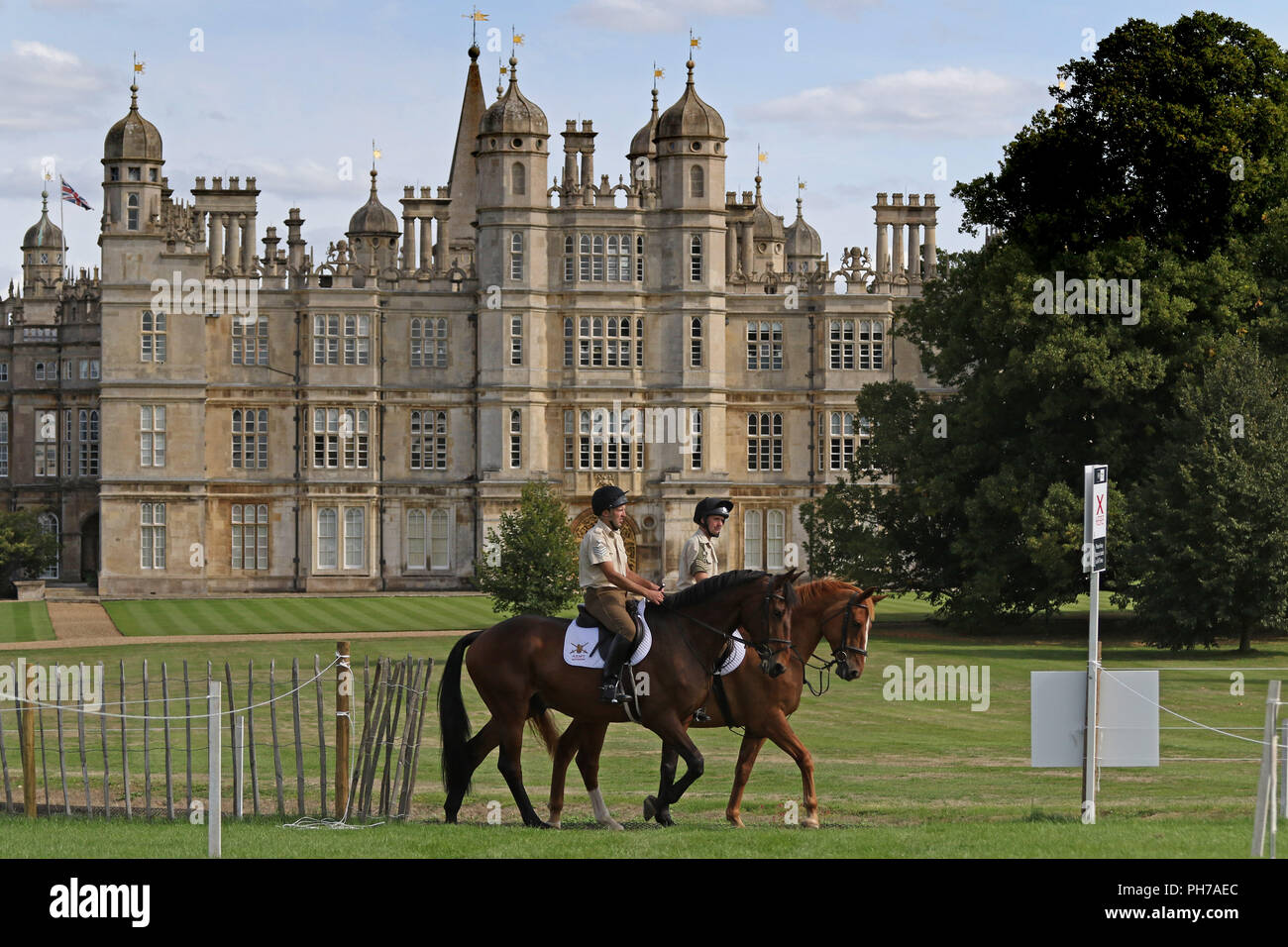 Stamford, UK. 30th Aug 2018. Soldiers of the Kings Troop Royal Horse Artillery (closest to camera) and The Household Cavalry go past Burghley House  on Day 1 of the 3 Day event at the Land Rover Burghley Horse Trials, at Burghley House, Stamford Lincs, on August 30, 2018. Credit: Paul Marriott/Alamy Live News - Stock Image