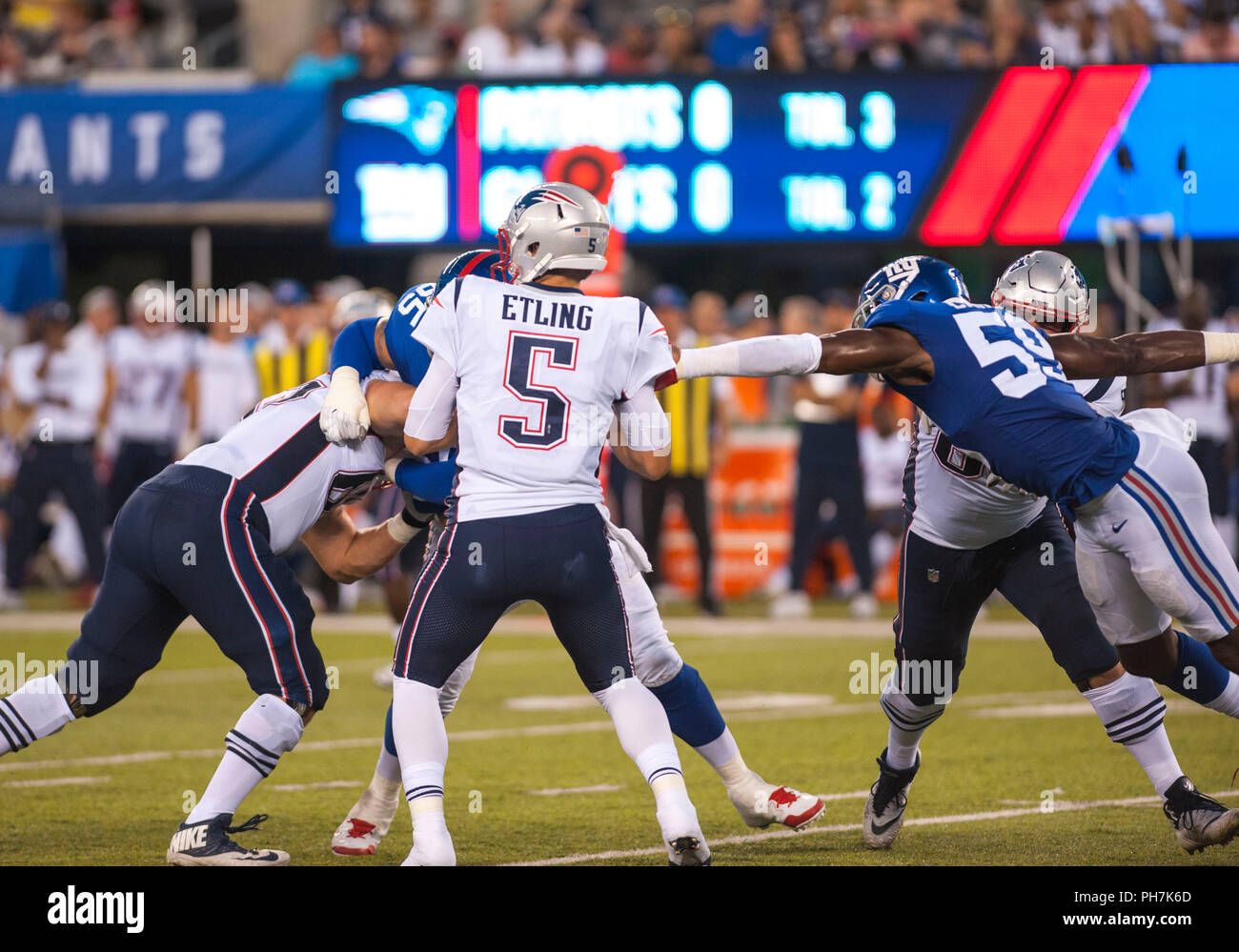 August 31, 2018 - East Rutherford, New Jersey, U.S. - New England Patriots quarterback Danny Etling (5) gets pressure from New York Giants linebacker Lorenzo Carter (59) during a preseason game between the New England Patriots and the New York Giants at MetLife Stadium in East Rutherford, New Jersey. Duncan Williams/CSM - Stock Image