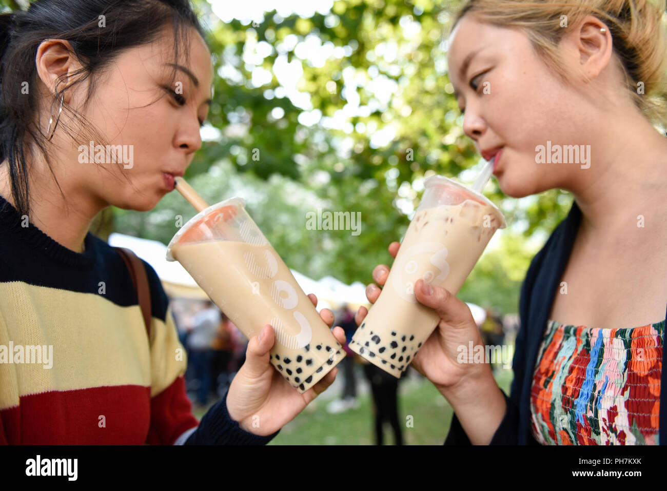 London, UK.  31 August 2018.  Girls enjoy a popular bubble tea drink on the opening day of the three day Chinese Food Festival at Potters Fields Park next to City Hall.  As well as food and drink from different parts of China freshly prepared for visitors to try, there are cooking demonstrations and presentations by the UK Han Culture Association.  Credit: Stephen Chung / Alamy Live News - Stock Image